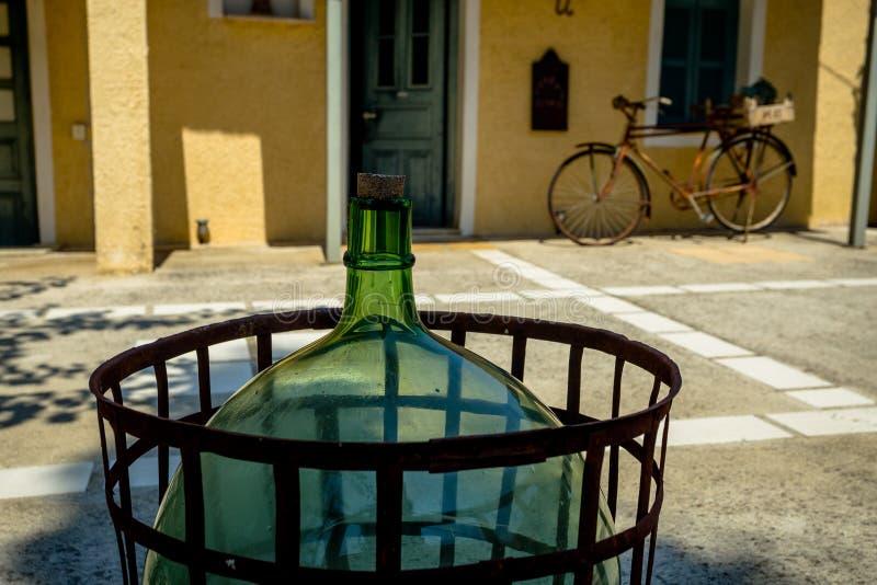 Une vieille bouteille de vin en verre dans la cour avec une vieille roue de bicyclette photos stock