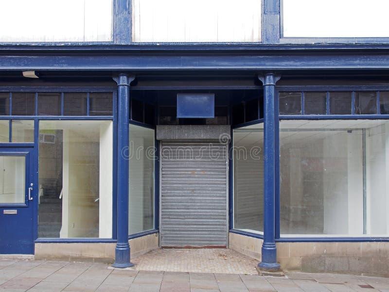 Une vieille boutique abandonnée peinte en bleu et blanc avec vitrine vide vitres sales et volets fermés à la porte image libre de droits