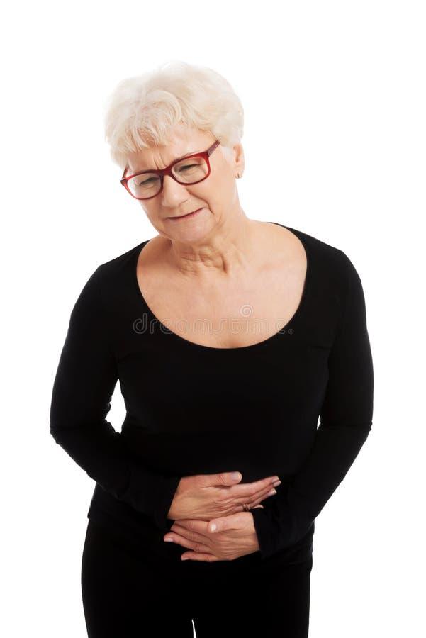 Une vieille dame a un mal de ventre. photographie stock libre de droits
