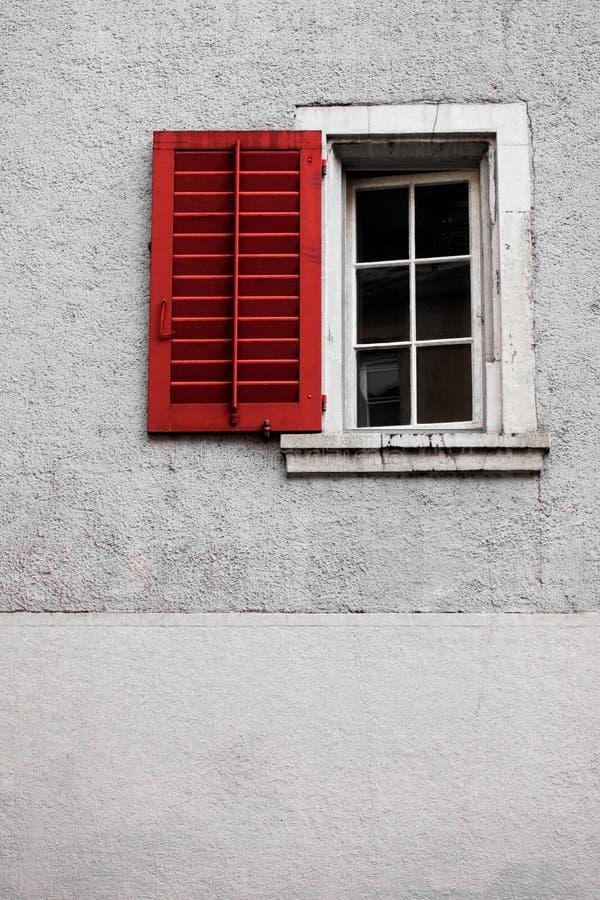 Une vieille fenêtre avec un volet rouge et un mur blanc image libre de droits