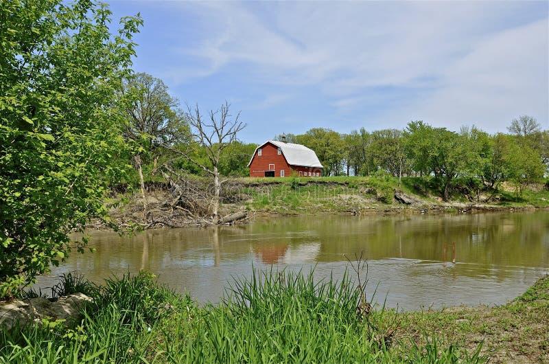 Une vieille grange rouge sur le bord de la rivière image stock