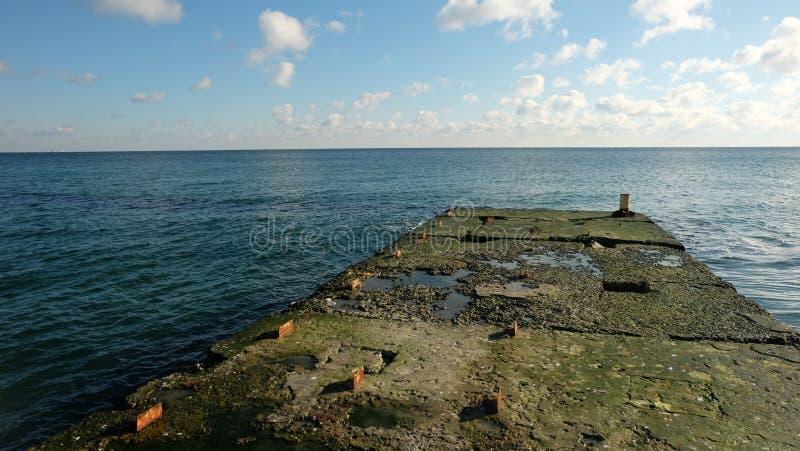 Une vieille jetée concrète près d'une mer calme photos stock