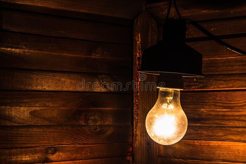 Une vieille lampe à incandescence illumine le coin d'une chambre noire Électrification, paiement pour l'électricité photo stock