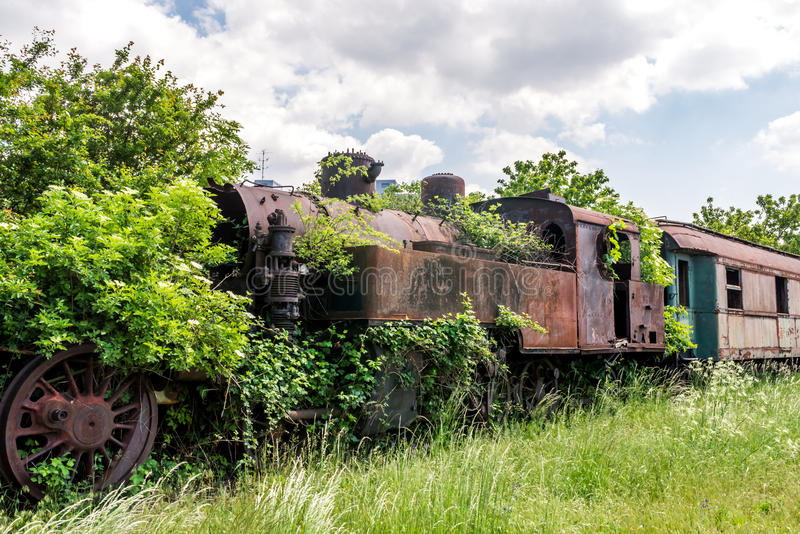 Une vieille locomotive à vapeur abandonnée et rouillée envahie avec des branches et des buissons verts se tenant sur un chemin de photo libre de droits