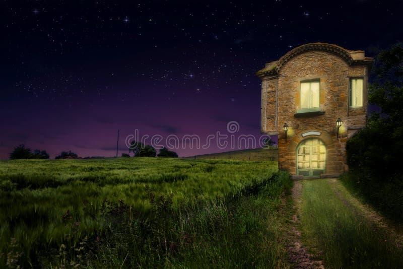 Une vieille maison de vintage près de champ de blé avec la lumière chaude à l'intérieur la nuit photo libre de droits