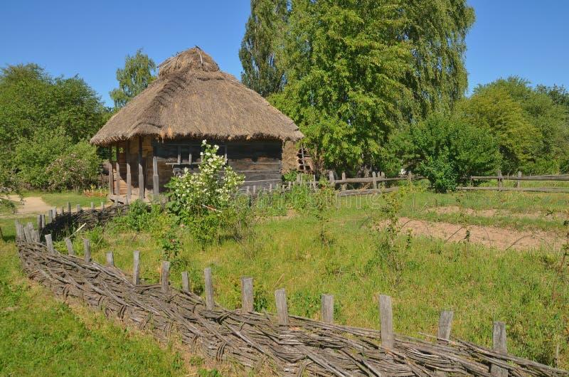 Une vieille maison en bois parmi les arbres et l'herbe image stock
