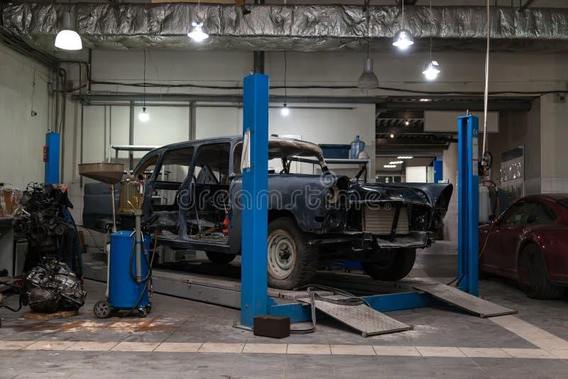 Une vieille rétro voiture classique des supports noirs de couleur sur un ascenseur bleu pour la réparation, la restauration et la images libres de droits
