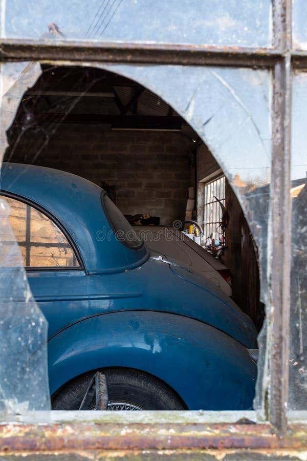 Une vieille voiture de Morris Minor par la fenêtre cassée d'un garage photos stock