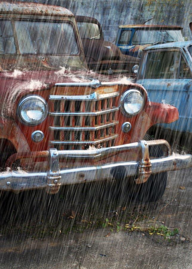 Une vieille voiture rouge de rouillement sous la pluie photos stock