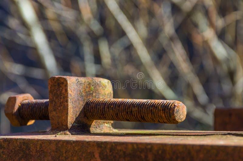 Une vis rouillée sur une construction en métal extérieure image libre de droits
