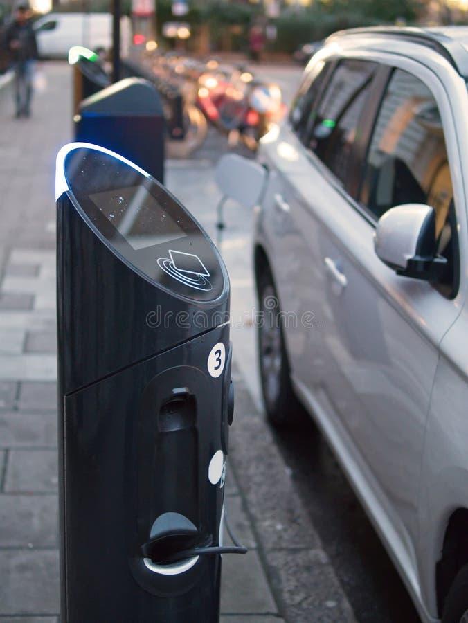 Une voiture électrique étant chargée à la station d'alimentation d'énergie photographie stock