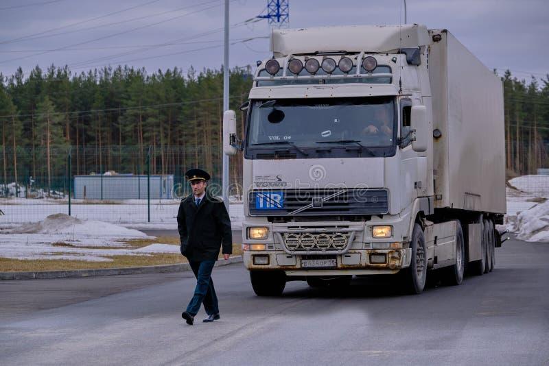 Une voiture avec des marchandises d'exportation sur le territoire de poste de douanes le représentant de l'organe d'état - le f image libre de droits