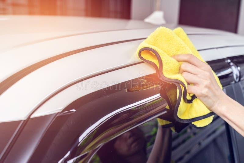 Une voiture blanche de nettoyage d'homme avec le tissu jaune de microfiber image libre de droits