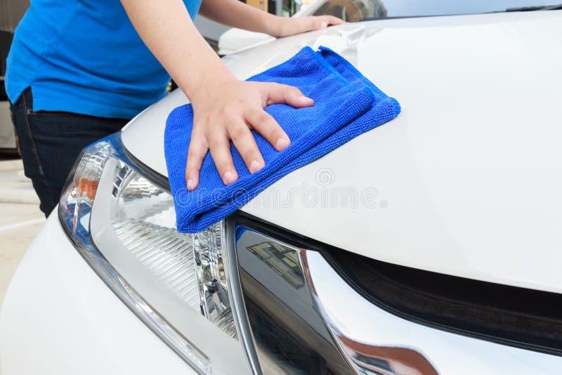 Une voiture de nettoyage de femme avec le tissu de microfiber, concept détaillant de voiture photo stock