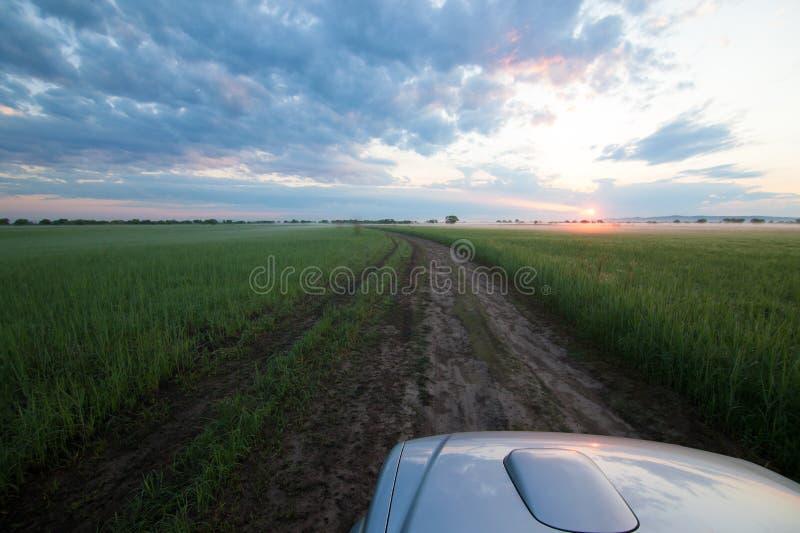 Une voiture est pêche allante et rencontre le lever de soleil dans un pré photographie stock libre de droits