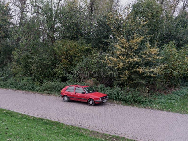 Une voiture rouge isolée se tient prêt la forêt image stock