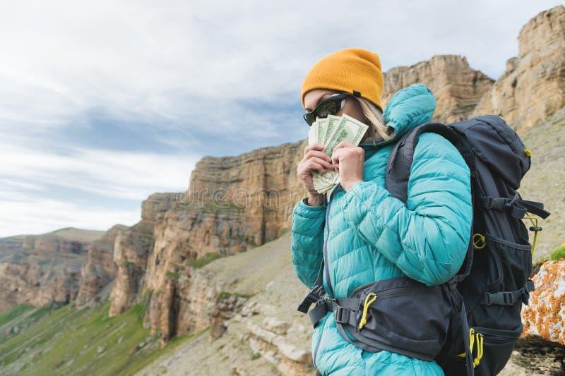 Une voyageuse de fille dans des lunettes de soleil et avec un sac à dos sur le fond des roches de haute montagne couvre son visag photographie stock