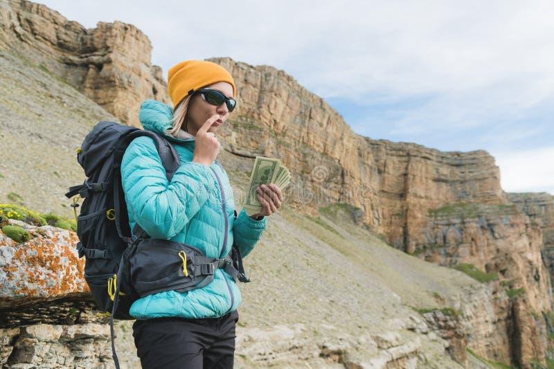 Une voyageuse de fille dans des lunettes de soleil et avec un sac à dos sur le fond des roches de haute montagne tient pensivemen images libres de droits