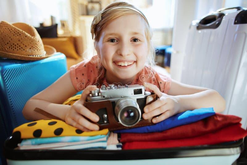 Une voyageuse souriante avec caméra rétrospective en valise photographie stock