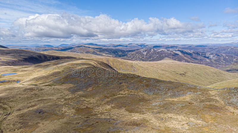 Une vue aérienne d'une gamme de montagne écossaise avec le chemin de petit lac et de traînée dans le premier plan sous un ciel bl image stock