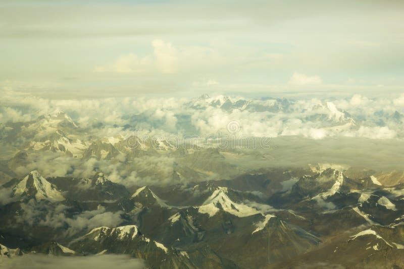 Une vue aérienne de la vallée de montagne de désert avec des crêtes de neige sous les nuages L'Himalaya Inde photos stock