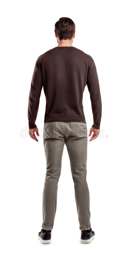 Une vue arrière sur un ajustement moderne et un homme en passant vêtu qui se tient dans une posture décontractée complètement dro image stock