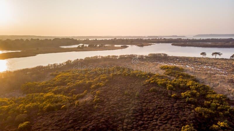 Une vue d'aerail de la réserve naturelle de Studland avec la dune de sable, le marais de tourbe et le lac sous un ciel bleu flou image libre de droits
