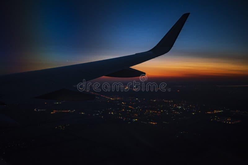 Une vue d'une fenêtre dans un avion, aile d'un avion photos stock