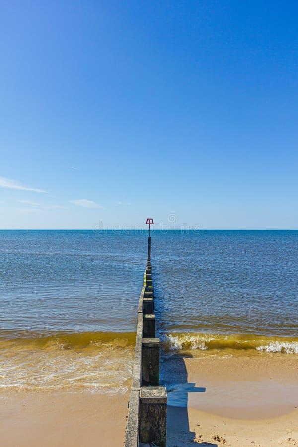 Une vue d'une plage sablonneuse avec un brise-lames de brise-lames et de mer calme sous un ciel bleu majestueux photos libres de droits