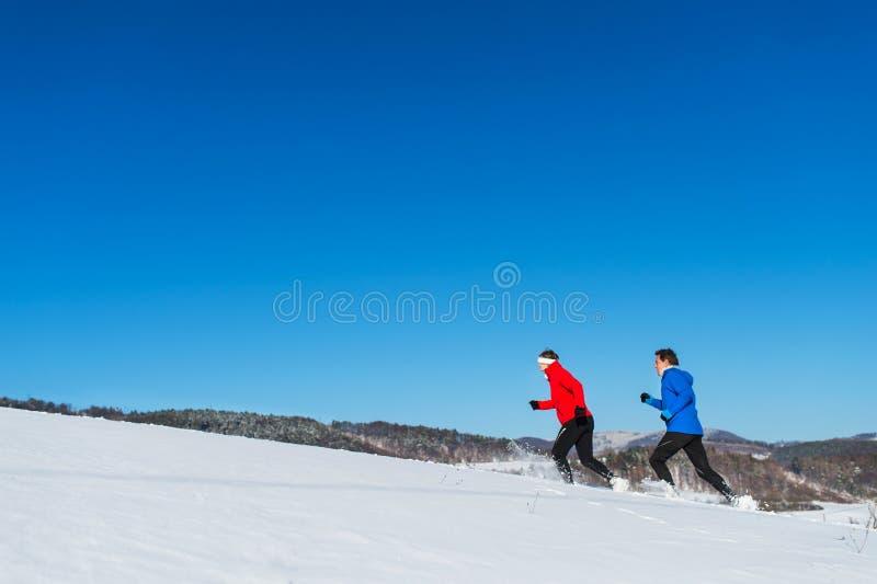 Une vue de côté des couples supérieurs pulsant en nature neigeuse d'hiver Copiez l'espace photographie stock