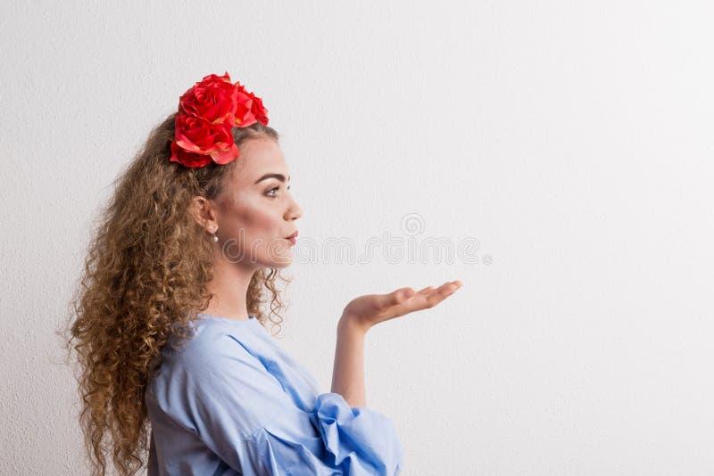 Une vue de côté de jeune belle femme avec le bandeau de fleur envoyant un baiser dans le studio image stock