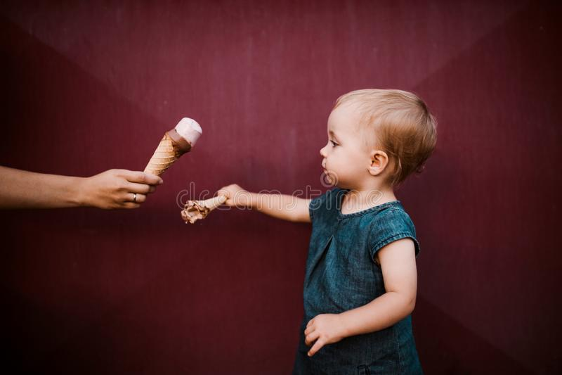 Une vue de côté de petite fille d'enfant en bas âge dehors en été, mangeant la crème glacée  photographie stock
