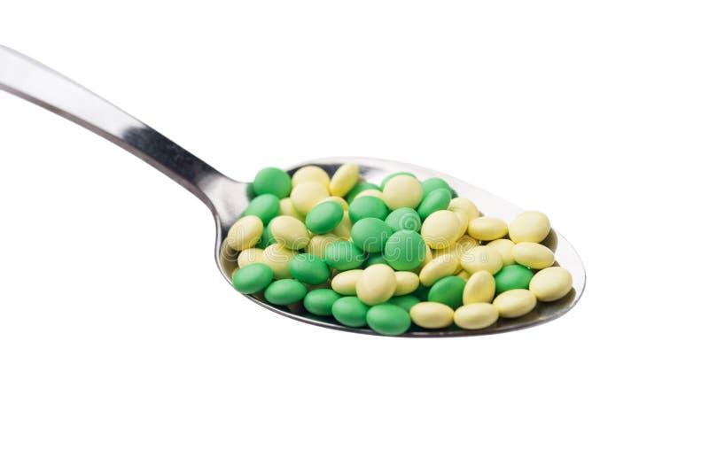 Une vue de côté d'un tas des pilules jaunes et vertes de médecine dans une cuillère images stock