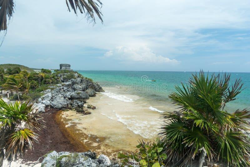 Une vue de la plage et de l'oc?an au-dessous du temple des ruines maya de Dieu de vent dans Tulum image libre de droits