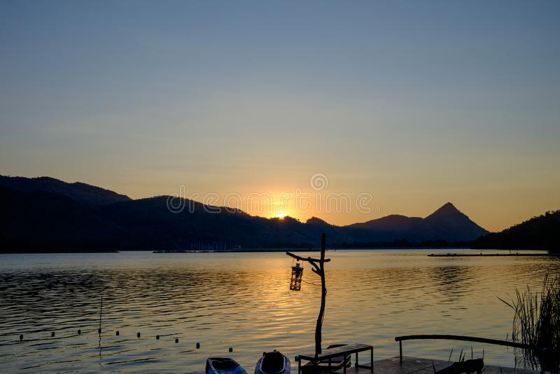 Une vue des montagnes et du lever de soleil ou coucher du soleil avec la lampe et le bateau flottant dans une rivière ou un lac photos libres de droits