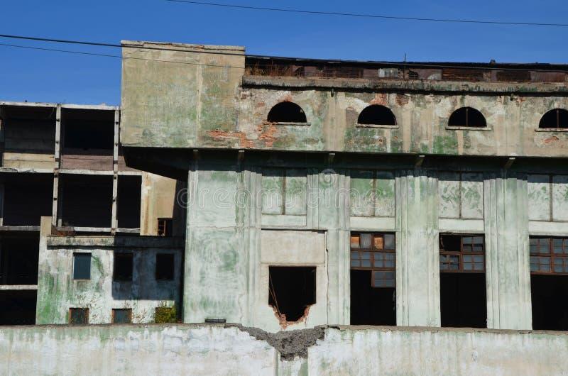 Une vue frontale des fenêtres abandonnées de fonderie a bourdonné image stock