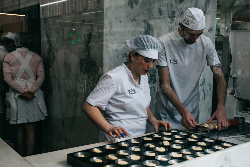 Une vue par la fenêtre d'un café ou le verre en tant que chef prépare un dessert portugais traditionnel appelé le Pastel de nata images libres de droits