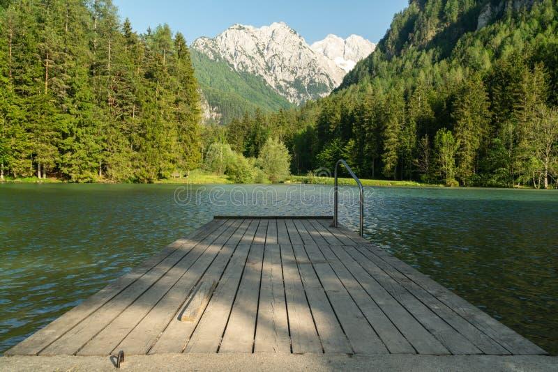 Une vue scénique des alpes prises au lac Jezersko, Slovénie Fond scénique et réflexion gentille de l'eau avec le pilier en bois photographie stock