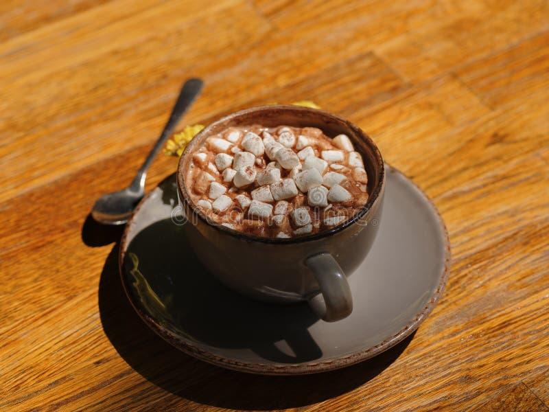 Une vue supérieure d'une boisson de cacao avec des guimauves Une tasse de café avec une cuillère et des fleurs sèches sur une tab images libres de droits