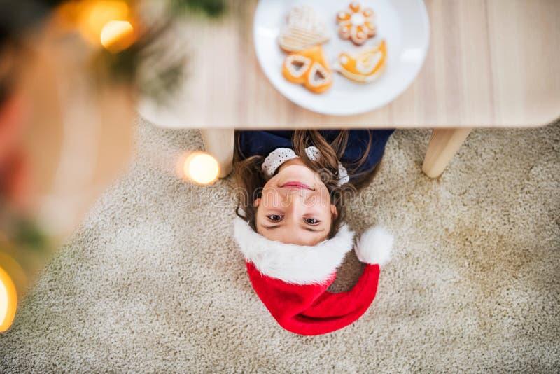 Une vue supérieure d'une petite fille avec le chapeau de Santa se trouvant sur le plancher au temps de Noël image libre de droits