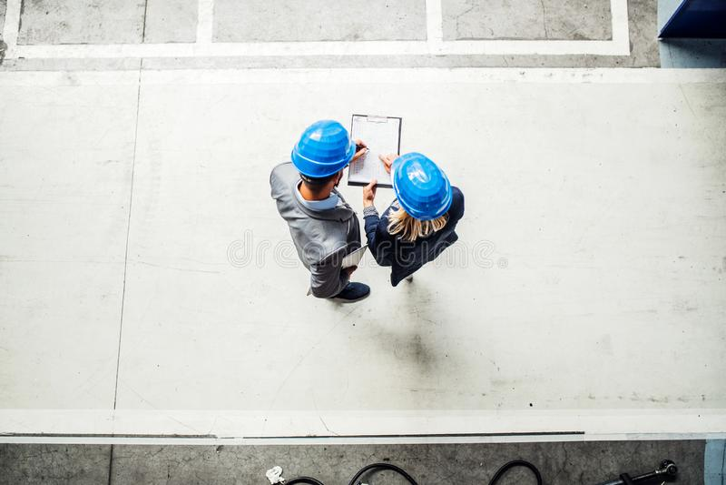Une vue supérieure d'un ingénieur industriel d'homme et de femme avec le presse-papiers dans une usine photos libres de droits