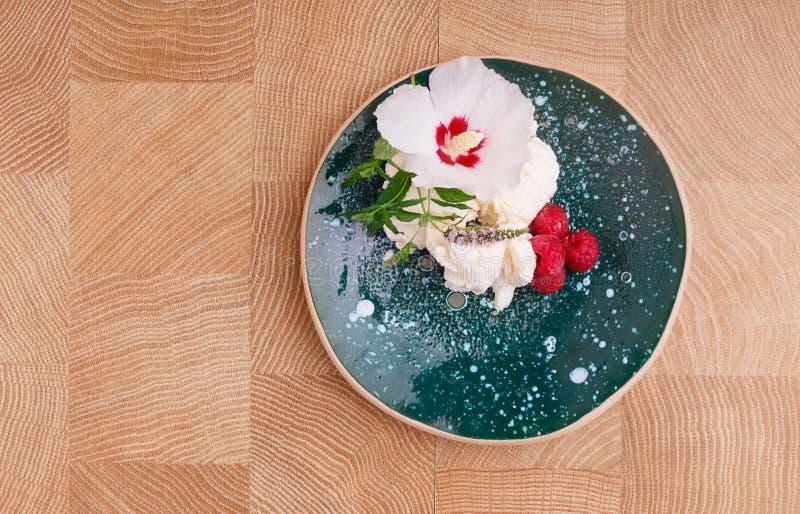 Une vue supérieure d'un plat complètement d'une crème glacée avec les framboises roses douces sur un fond en bois Casse-croûte or image stock