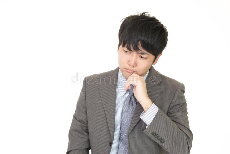 Uneasy Asian businessman stock images