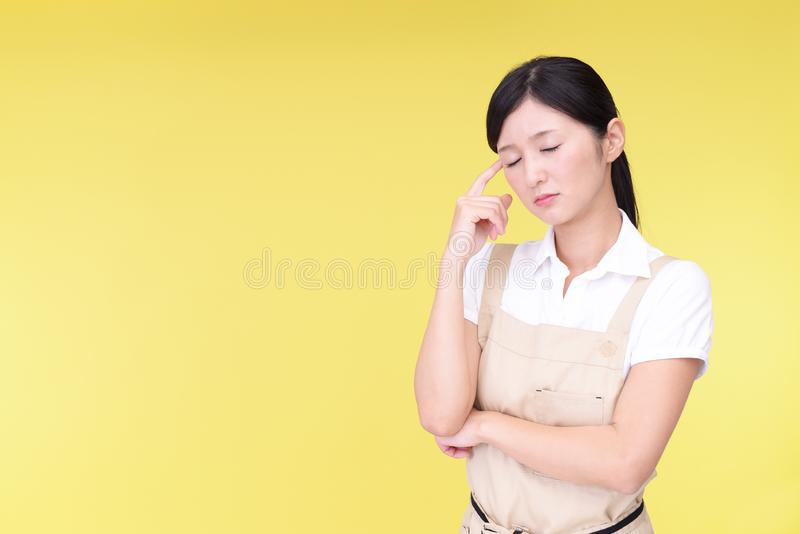 Uneasy Asian woman in apron stock photography