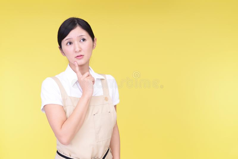 Uneasy Asian woman in apron royalty free stock photography