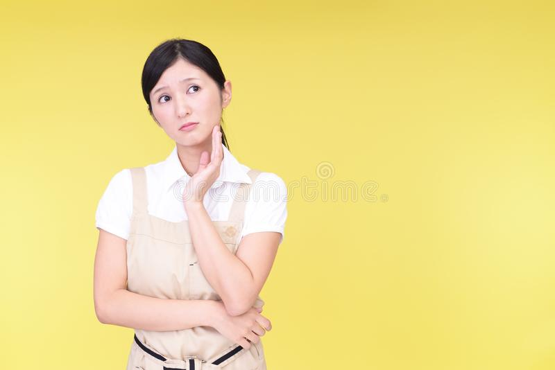 Uneasy Asian woman in apron stock photos
