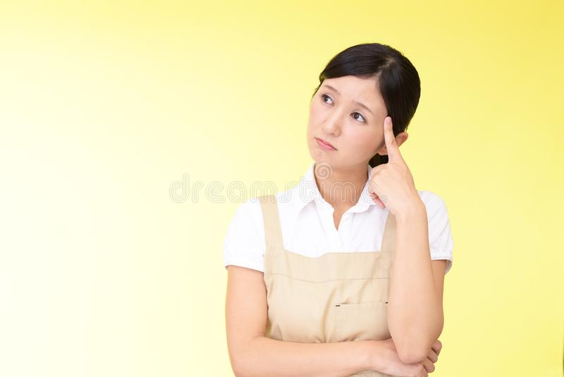 Uneasy Asian woman in apron royalty free stock photo