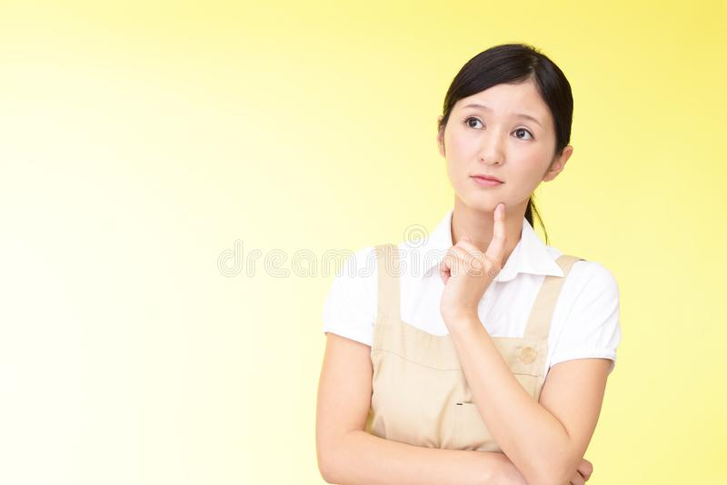 Uneasy Asian woman in apron stock images
