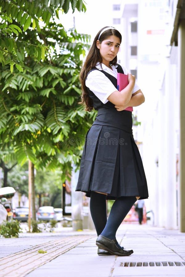 Unemotional Śliczna Kolumbijska Studencka nastolatek szkoły dziewczyna Jest ubranym mundurek szkolnego Z notatnikiem obraz royalty free