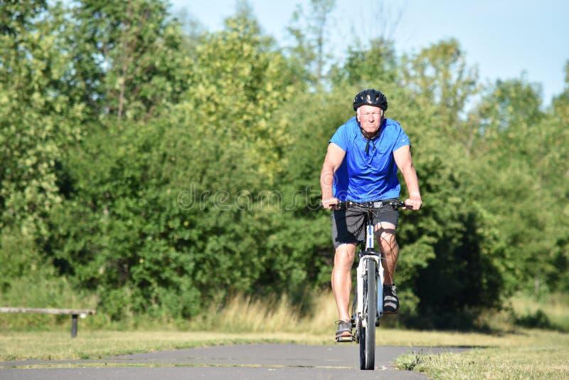 Unemotional Dorosłej samiec atlety Jechać na rowerze obrazy royalty free